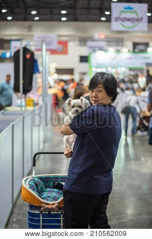 Asian Woman And The Dog In Exhibit Hall Or Expo