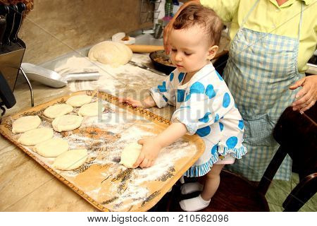 Woman Baking Pies In Kitchen With Little One-two Granddaughter. Grandma Learn Child. Making Pie By H