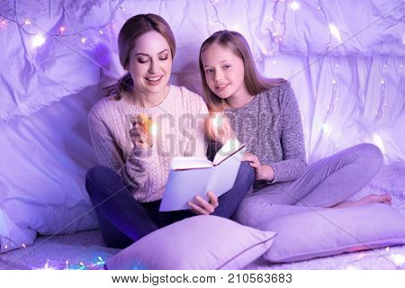We love reading. Happy young involved mother and daughter reading a book and holding torches while sitting