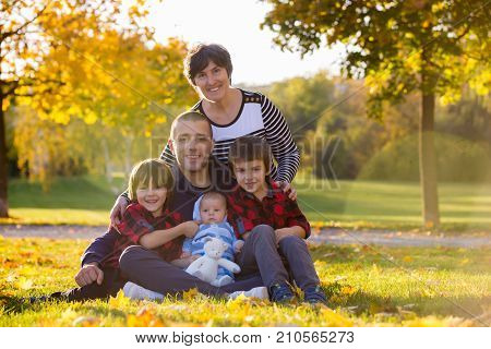 Three generation family playing in the park having portrait autumn time. Family concept