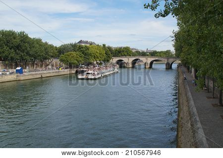 The Seine in Paris - France. The Seine in Paris is a part of the landscape of the capital of France. The Seine cuts Paris in its environment (middle) even if the right bank occupies a space more important than the left bank. In Paris, its length occupies