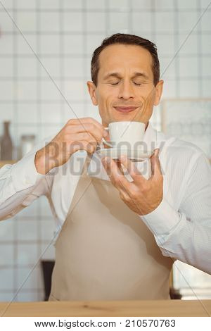 Wonderful smell. Happy delighted cheerful man holding a cup of coffee and smelling it while enjoying the smell