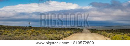 Panoramic Karoo scene in South Africa, a dirt road stretches to the horizon with a windmill pump in the background