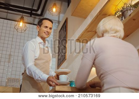 Working with customers. Pleasant handsome friendly waiter holding plates with food and serving breakfast while being at work
