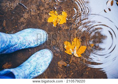 woman legs walking in puddle in rubber boots