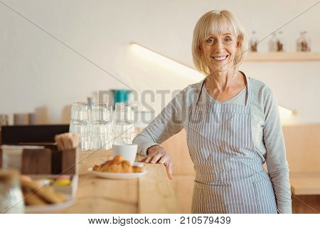 Bakery owner. Happy delighted elderly woman smiling and looking at you while working in the bakery