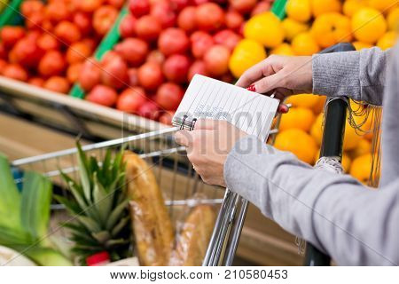 Woman with notebook in grocery store choosing vegetables, holding shopping list