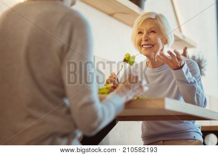 At lunchtime. Delighted senior pleasant woman smiling and eating a salad while having a pleasurable meeting with her friend