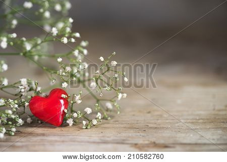 Small red heart from glass and white flowers on a rustic wooden background with generous copy space love concept for christmas mother's day and valentine's day closeup