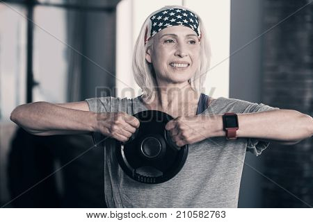 Muscle-strengthening exercises. Beautiful joyful senior woman standing in the gym, holding a weight disc with both hands lifted, keeping elbows parallel to the floor