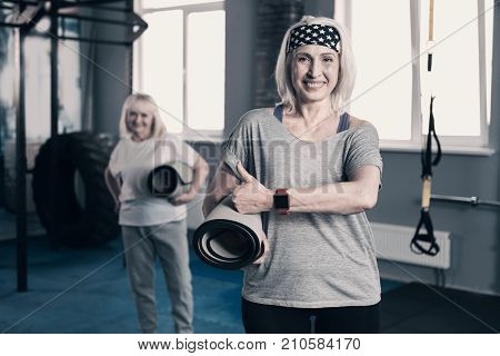 I love yoga. Lively elderly woman holding a yoga mat and giving a thumbs up while her friend standing in the background and holding a yoga mat as well