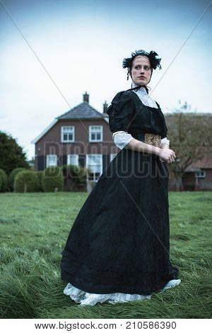 Historical Woman In Black Dress In Countryside At Farm