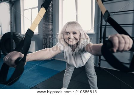 Stretching with pleasure. Adorable petite senior woman doing trunk bending with a suspension trainer while smiling broadly at the camera