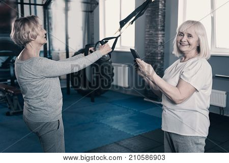 Enjoying themselves. Pleasant lively senior woman taking a photo of her peer friend working out with a suspension trainer
