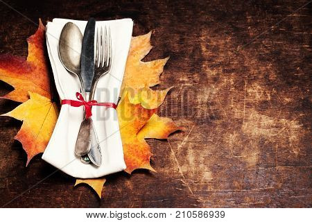 Thanksgiving table setting - Seasonal cutlery on rustic wooden table. Autumn holiday background with knife fork and spoon.