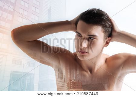 Calmness. Self assured young serious man looking to the right with his hands behind his head