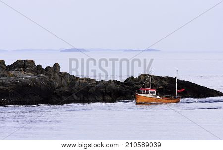 ØLBERG, SOLA, NORWAY ON JULY 06. View of a fishing-boat heading for the inlet on July 06, 2009 in Ølberg, Norway. Calm sea, islands in the background. Editorial use.