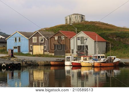 ØLBERG, SOLA, NORWAY ON JULY 06. View of boats, cabins and a fortress by a harbor on July 06, 2009 in Sola, Norway. Storehouse and warehouse this side the hill. Editorial use.