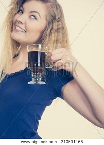 Positive woman holding black coffee about to drink. Getting morning energy hurry up before going to work.