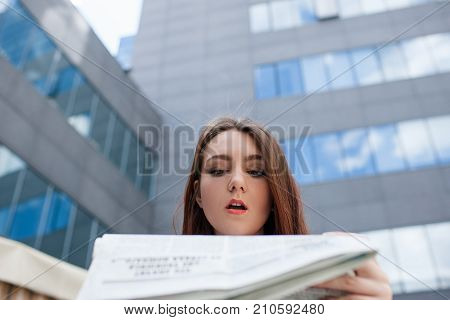 surprised amazed astonished woman. unexpected newspaper news concept