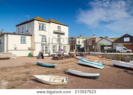 Teignmouth Devon England 18 July 2016: Very old pub - New Quay Inn. Coast River Teign. Fishing boats in the foreground. Devon