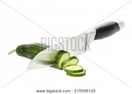 chef knife slicing a cucumber on white