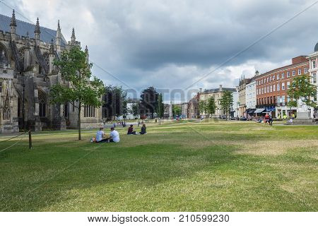 Exeter Devon England 22 July 2016: Resting people on the lawn near the cathedral