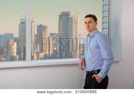 Man experienced managing director dressed in luxury suit is resting after conference with his staff while is standing near office window background with copy space for your advertising text message. skyscrapers