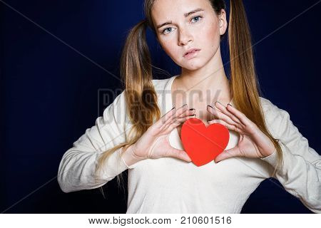 girl in a white sweater and with two tails holds a paper heart in her hands and snort to the camera, isolated