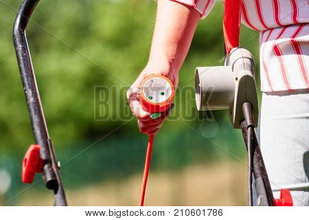 Gardening. Female person being mowing green lawn with lawnmower in sunny day.