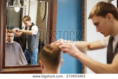 Young barber making haircut at barbershop, closeup. Client looking at mirror. Hipster barbershop for men
