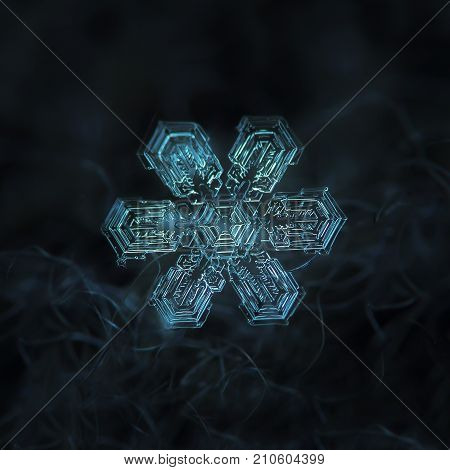 Real snowflake macro photo: large star plate snow crystal with big hexagonal center and six straight, broad arms with complex, ornate inner pattern. Snowflake glowing on dark blue textured background.