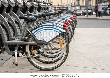 Healthy, ecological transport concept. Rental bikes parking lot. Row bicycle wheels in the city sidewalk