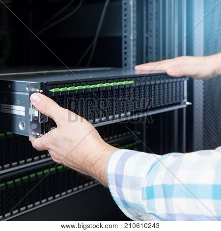 IT Engineer rackmount many hard disks drive in enclosure in the storage system in the data center
