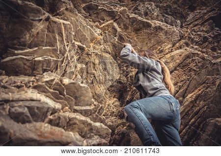 Courage woman achieving her goal climbing up on rock