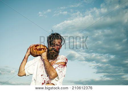 Halloween Hipster Holding Pumpkin On Cloudy Blue Sky