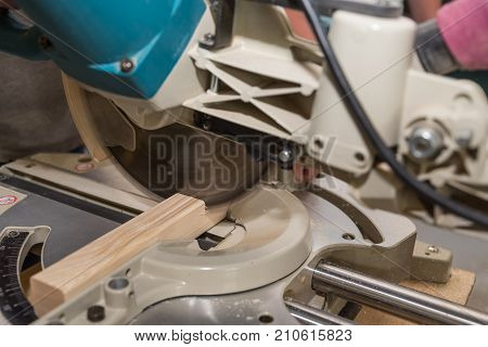 Person saws apart with wooden table saw - closeup