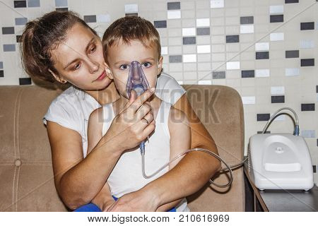 Inhaler for cough. Mom makes his son inhalation for bronchitis from coughing. Breathe in inhaler mask. treatment of children's respiratory illness