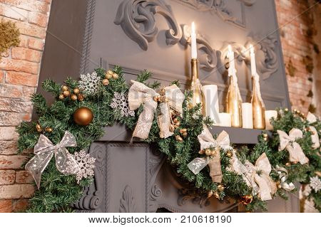 Christmas tree branch on fireplace and other holiday decorations in dark loft. candles