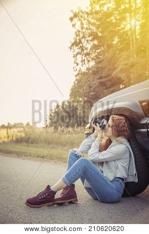Travel. Beautiful redhair girl sitting on the road with camera