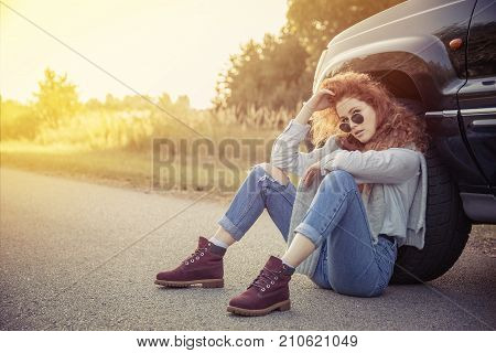 Travel. Beautiful Redhair Girl Sitting On The Road