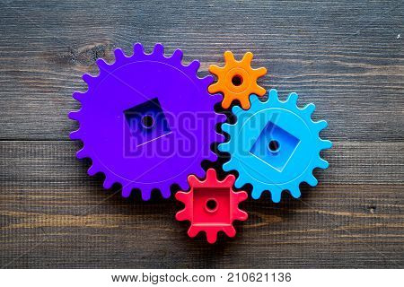 moving forward concept, ideal operating principle with gears and wheels on wooden desk background top view mock up