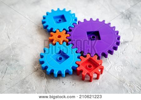 moving forward concept, ideal operating principle with gears and wheels on stone desk background