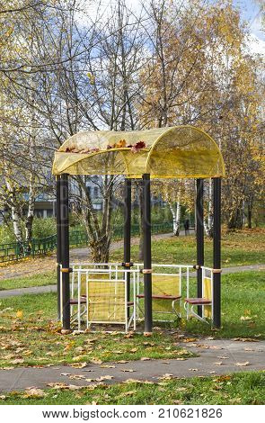 Metal gazebo sprinkled with autumn leaves of maple