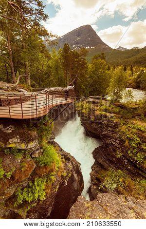 Tourist attraction in Norway Europe. Woman photographer taking photo with camera on Gudbrandsjuvet viewpoint Valldalen valley between Valldal and Trollstigen.