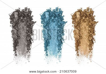 Set of eyeshadow sample isolated on white background. Crushed brown golgen, black and blue metallic eyeshadow. Closeup of a makeup product
