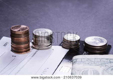 Money - Forms of payment on a dark background.  Coins, paper money, a check, and a credit card