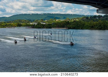 A formation of high-speed personal watercraft zooms into view on the Tennessee River in Chattanooga