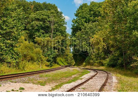A trailroad track and siding merge before heading into a wooded area