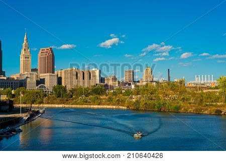 A lone motorboat plies a bend of the Cuyahoga River beneath the towers of downtown Cleveland Ohio